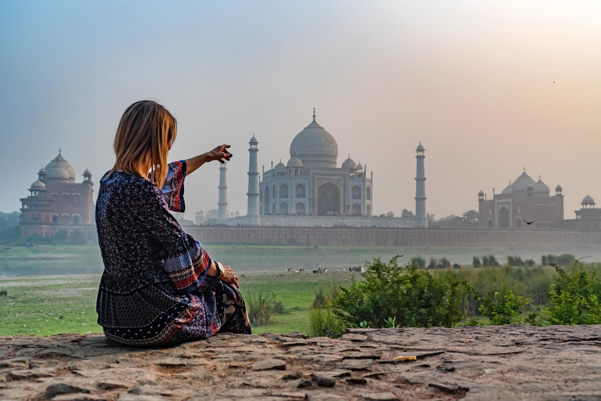 Beautiful girl points to Taj Mahal.